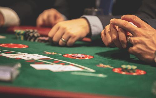 Los mejores consejos de blackjack: foto de las manos de los jugadores en la mesa de blackjack
