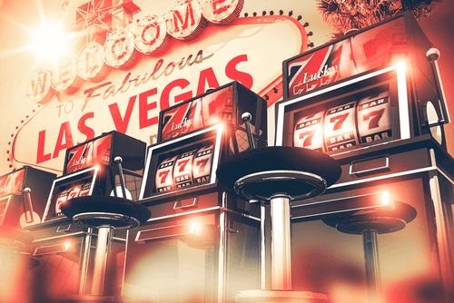Beste Casino Slots zum Spielen - Illustration von Spielautomaten in einer Reihe vor dem Vegas Sign