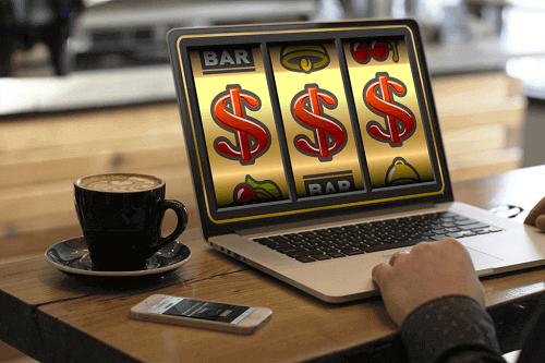 Echtgeld-Slots-Spiele - Foto des Mannes, der Spiel auf Laptop spielt