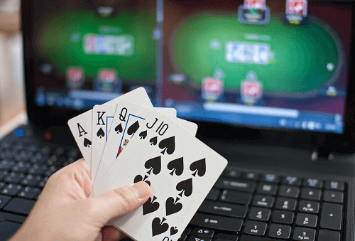 Top Online Blackjack Games - Picture of Hand Holding Cards in Front of Laptop